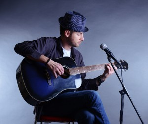 Young musician playing acoustic guitar and singing, on gray back